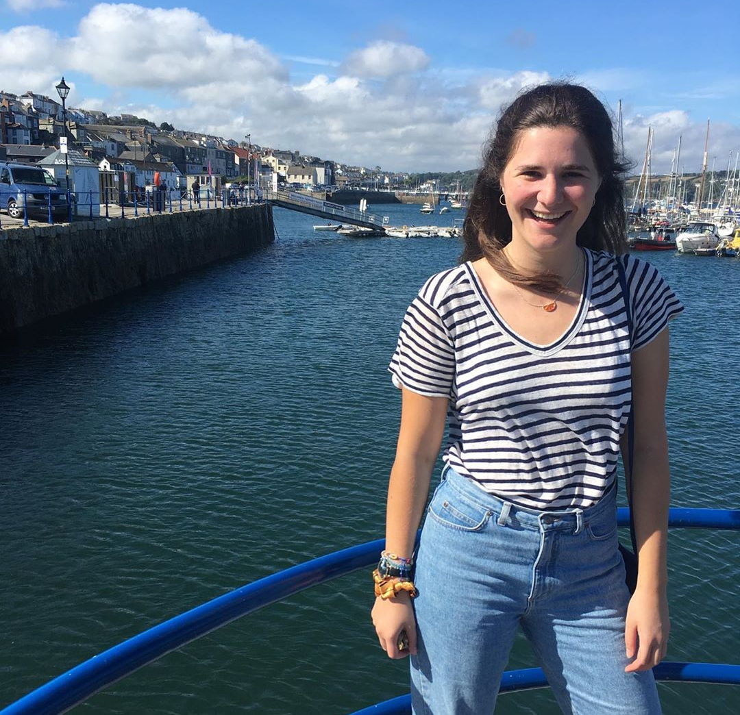 Brunette girl smiling and posing in front of a harbour. She's wearing a black and white striped t=shirt and blue jeans. It's sunny.