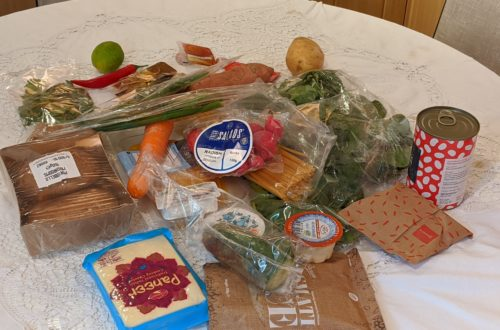 lots of ingredients on a kitchen table. many of them are wrapped in plastic packaging.